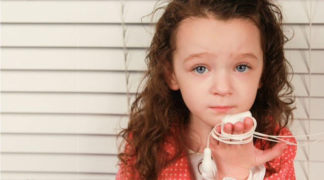Girl holding cord window blinds - Go Cordless