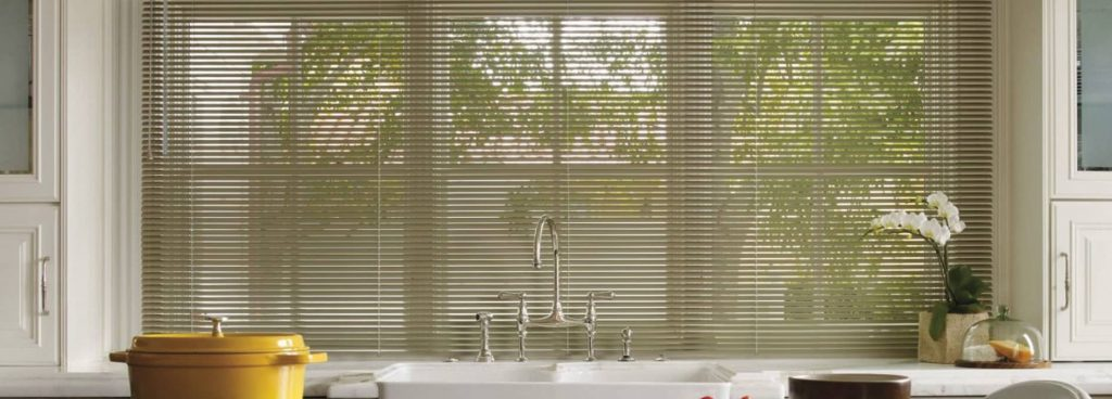 kitchen sink in fromnt of a window with aluminum blinds