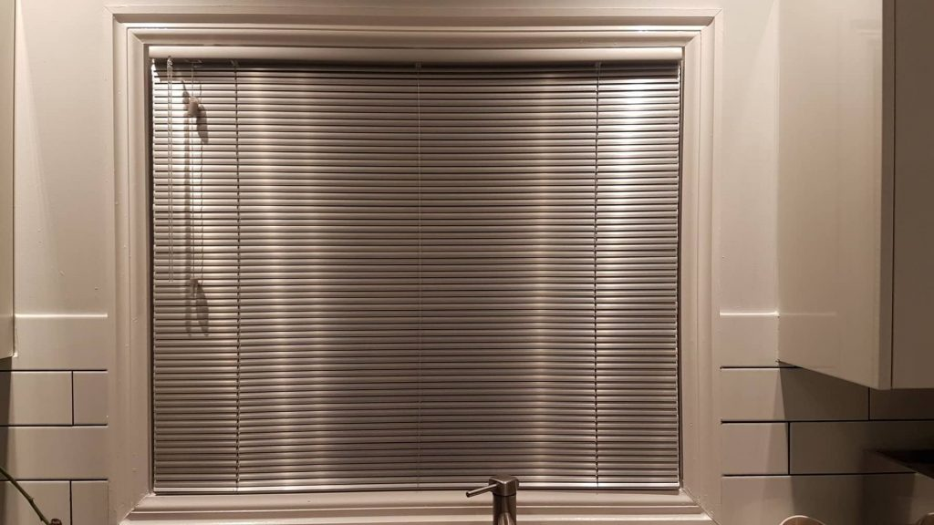 window in a kitchen with aluminum blinds