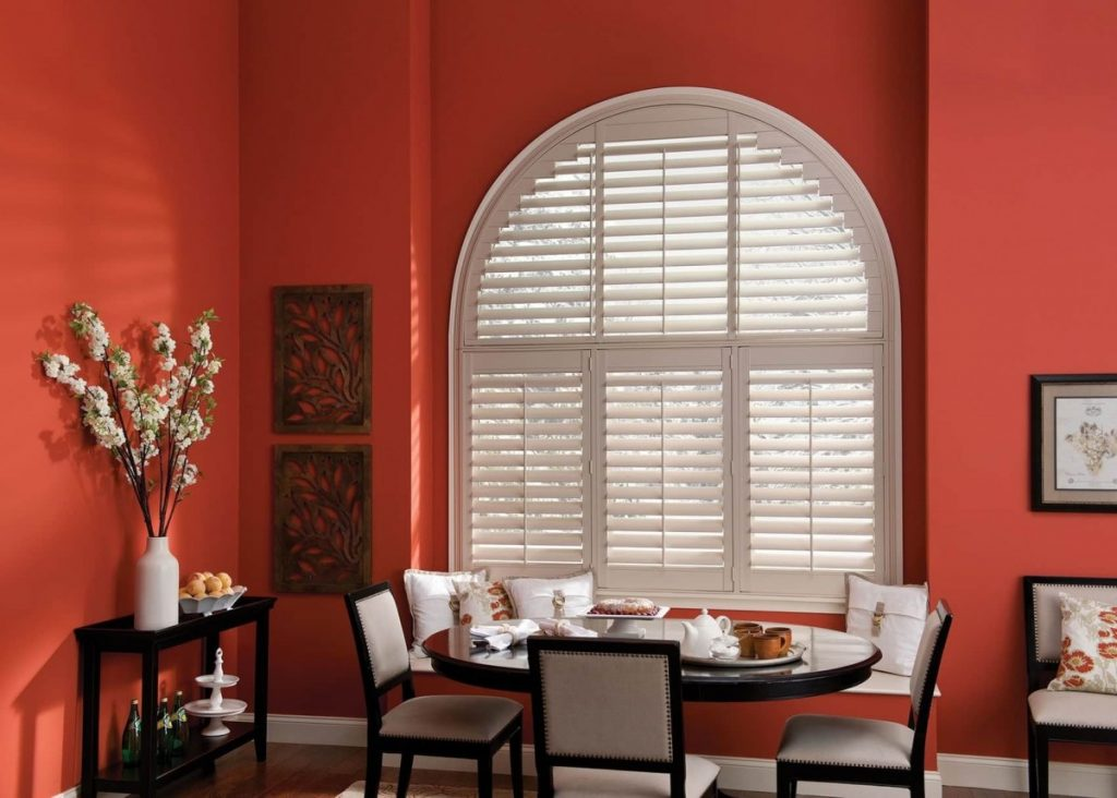 shutters on an arched window in a dining room